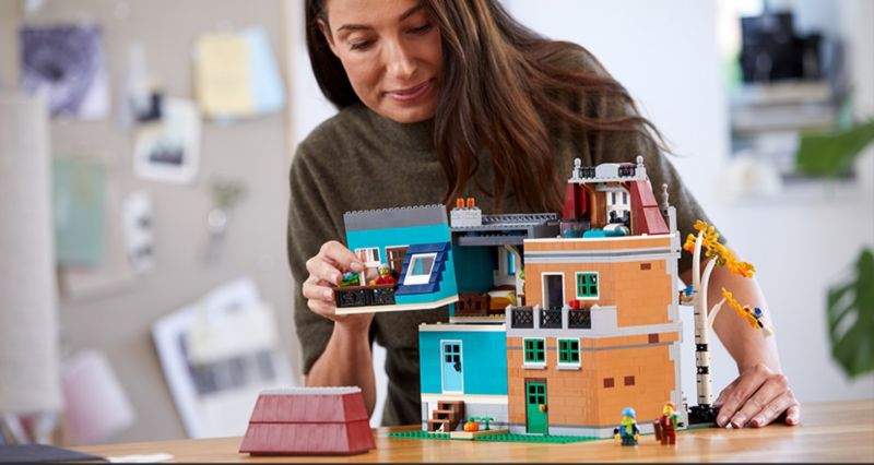 LEGO Creator Expert Bookshop modular - woman removing townhouse roof to look in side